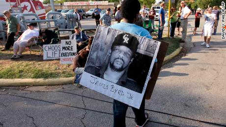Ricky Jason, a friend of Ross Byrd's, wears a photo of James Byrd before Russell Brewer's execution.