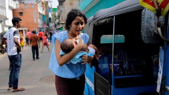 A woman carrying an infant runs for safety after police found a suspicious vehicle parked in Colombo, Sri Lanka, on Monday, April 22, a day after several coordinated bombings across the country killed hundreds.