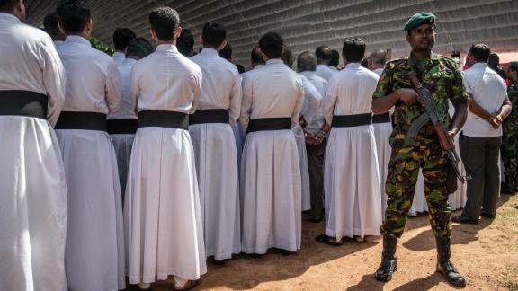 A soldier stands guard next to members of the clergy during a mass funeral in Negombo on Tuesday.