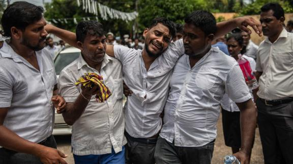 A man is supported as he follows a coffin during a mass funeral for bombing victims at St. Sebastian Church in Negombo, Sri Lanka, on Tuesday, April 23.