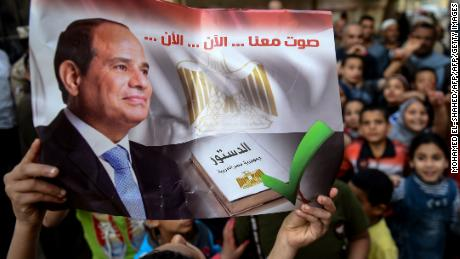 "An Egyptian man outside a polling station holds a banner reading: ""Vote with us... now... now."""