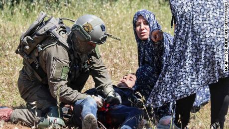 An Israeli soldier performs first aid at Al-Badan.