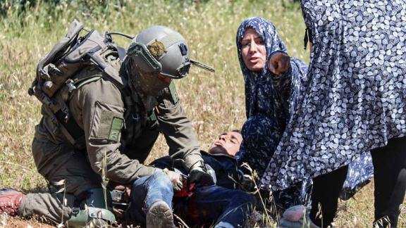 An Israeli soldier performs first aid on al-Badan.