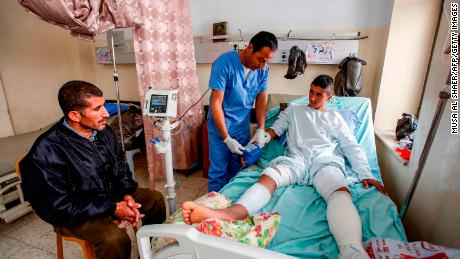 Al-Badan (right) gets treatment at Beit Jala Hospital near Bethlehem, as his father (left) is watching.
