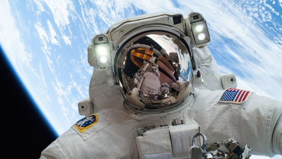 On Dec. 24, 2013, NASA astronaut Mike Hopkins, Expedition 38 Flight Engineer, participates in the second of two spacewalks, spread over a four-day period, which were designed to allow the crew to change out a degraded pump module on the exterior of the Earth-orbiting International Space Station. He was joined on both spacewalks by NASA astronaut Rick Mastracchio, whose image shows up in Hopkins' helmet visor. The pump module controls the flow of ammonia through cooling loops and radiators outside the space station, and, combined with water-based cooling loops inside the station, removes excess heat into the vacuum of space. Image Credit: NASA