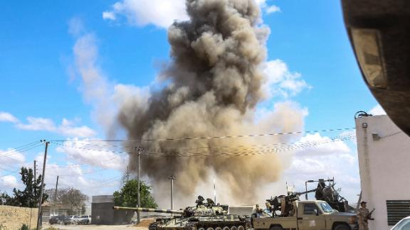 Smoke rises from an airstrike behind a tank and improvised fighting truck belonging to forces loyal to Libya