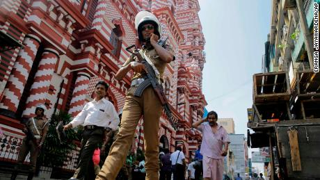 A Sri Lankan police officer patrols outside a mosque in Colombo, Sri Lanka