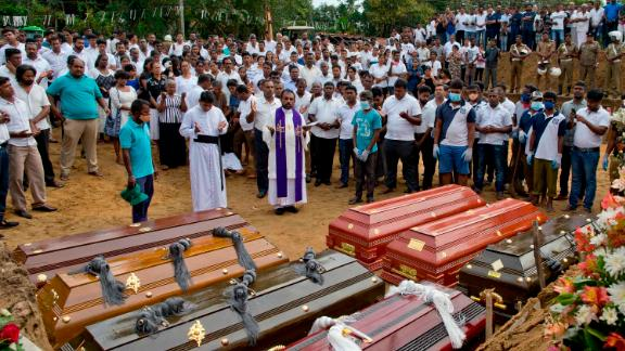 A priest conducts a burial ceremony for victims of the Easter Sunday bombings in Negombo, Sri Lanka, on Wednesday, April 24.