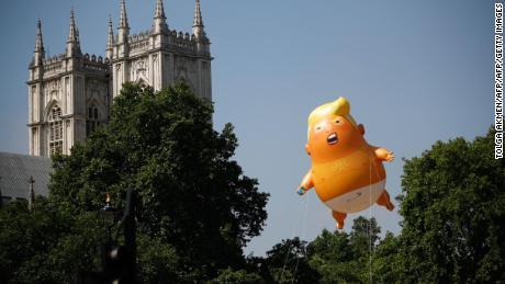 Fußgänger gehen vorbei, während ein riesiger Ballon, der US-Präsident Donald Trump zeigt, wie ein orangefarbenes Baby neben den Türmen der Westminster Abbey schwebt, während einer Demonstration gegen Trumps Besuch in Großbritannien auf dem Parliament Square in London am 13. Juli 2018.
