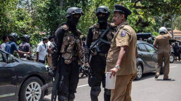 Military personnel talk with a police officer near the site where a package, believed to be a bomb, was detonated in a controlled explosion after being discovered in a nearby restaurant in Negombo on Wednesday, April 24.
