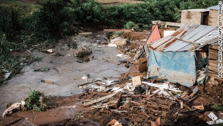 People abandon their homes after they were destroyed by torrential rains and flash floods at an informal settlement of BottleBrush, south of Durban, on April 23.