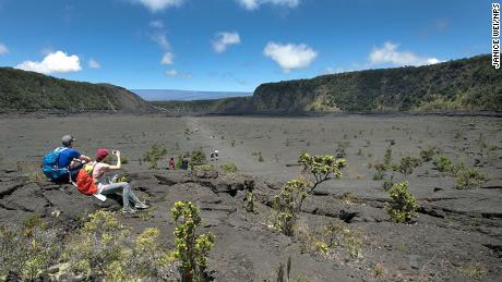 Park visitors stop for a rest and a photo opportunity on Kīlauea Iki Trail