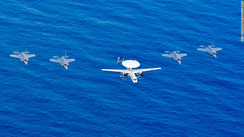 A US Navy carrier-based E-2D Hawkeye airborne radar plane and four US Marine Corps F-35B Lightning jets fly over the South China Sea.