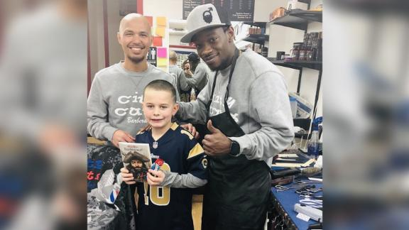 City Cuts owner Jon Escueta and barber Jerry Jones pose with 8-year-old Connor after a haircut.