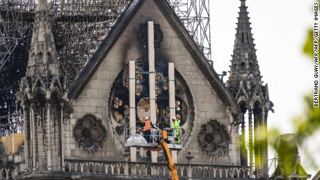 TOPSHOT - Workers intervene on the northern side of Notre-Dame Cathedral in Paris on April 18, 2019, three days after a fire devastated the landmark in the centre of the French capital. - France paid a daylong tribute on April 18, 2019 to the Paris firefighters who saved Notre Dame Cathedral from collapse, while construction workers rushed to secure an area above one of the church's famed rose-shaped windows and other vulnerable sections of the fire-damaged landmark. (Photo by BERTRAND GUAY / AFP)        (Photo credit should read BERTRAND GUAY/AFP/Getty Images)
