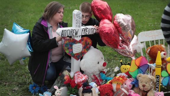 Angela Krambeer and her son Dylan visit a memorial outside AJ's home.