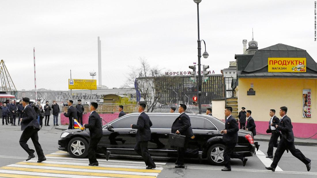 North Korean security staff members run with a car carrying leader Kim Jong Un at Vladivostok Station on Wednesday, April 24, in Vladivostok, Russia.