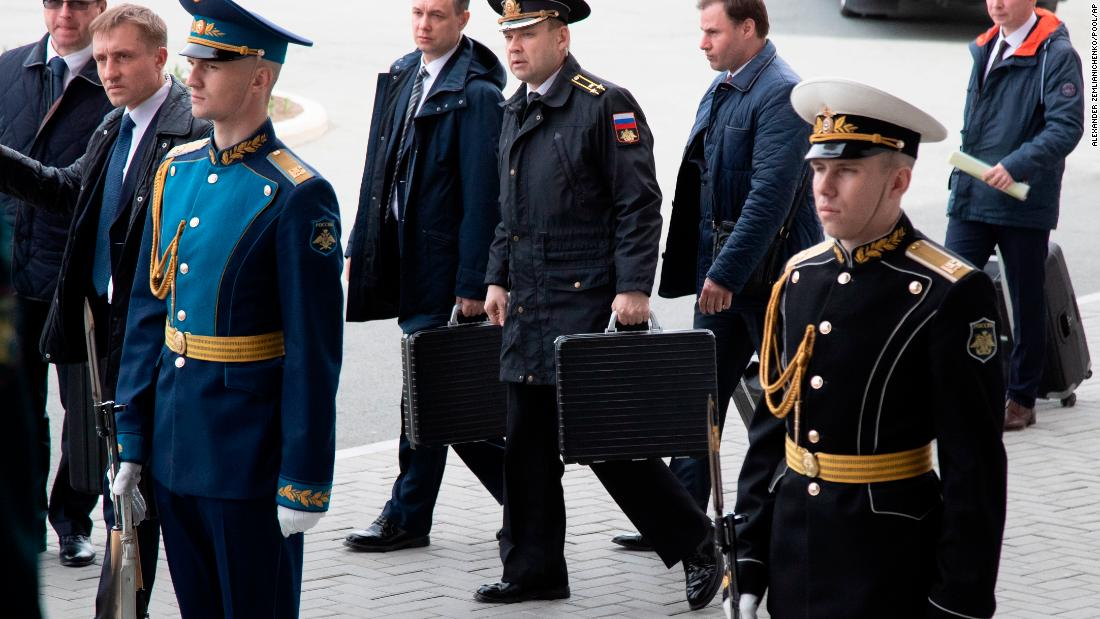 Russian officers carry briefcases that appear to contain nuclear launch codes as Russian President Vladimir Putin arrives for talks with North Korea's leader Kim Jong Un in Vladivostok, Russia, Thursday, April 25.