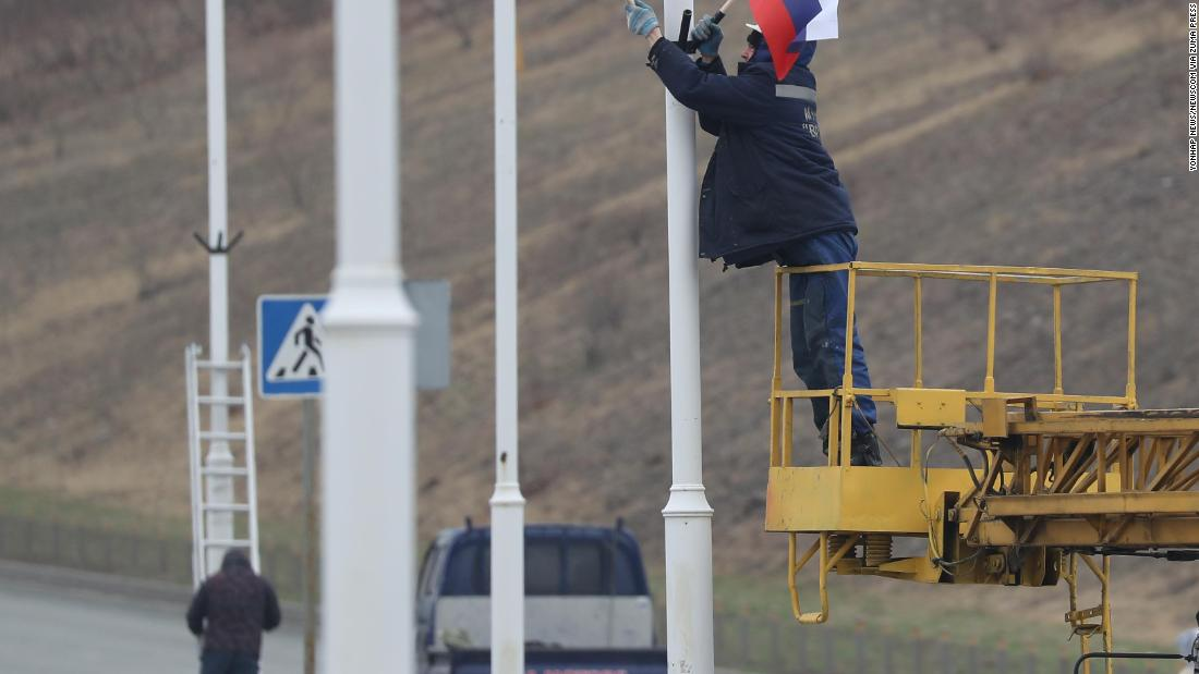 Workers hang the North Korean and Russian flags on a road leading to the Far Eastern Federal University on Wednesday, April 24, in advance of the summit between North Korean leader Kim Jong Un and Russian President Putin.