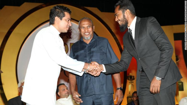 Spice trader Mohamed Ibrahim, center, looks on as his son Imsath, right, shakes the hand of a government minister, in a 2016 photo.