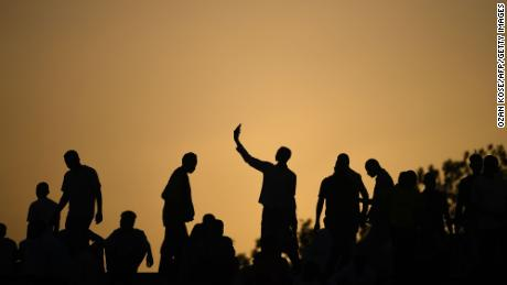 TOPSHOT - Silhouettes of Sudanese protesters are seen during a protest outside the army headquarters in the capital Khartoum on April 22, 2019. - Sudan's new army rulers on April 21 ordered protesters to dismantle their barricades on roads leading to the military headquarters as tensions grew after talks between the two sides broke down. The demonstrators have accused the ruling military council of being little different from veteran leader Omar al-Bashir who was topped by the army on April 11 following months of street protests. (Photo by OZAN KOSE / AFP)        (Photo credit should read OZAN KOSE/AFP/Getty Images)