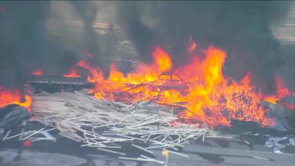 Video from the scene showed towering orange flames and piles of lumber scattered across the highway.
