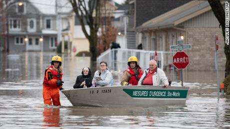 Firefighters evacuate residents of Sainte-Marie, Quebec, after the Chaudière River burst its banks.