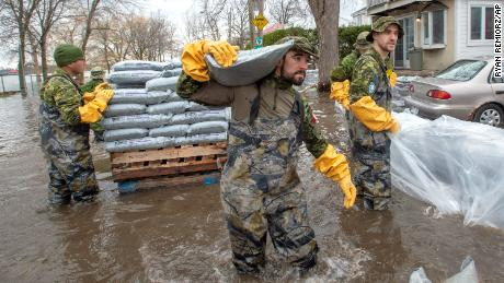Canadian Forces personnel sandbag a house against floodwaters Thursday in Laval, Quebec.