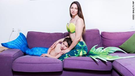 In this Wednesday, Feb. 27, 2019 photo, Shir Katzenell and her son Erez, members of the Israeli Mermaid Community, pose for a portrait as they wear mermaid tails at their home in Or Akiva, Israel. (AP Photo/Oded Balilty)