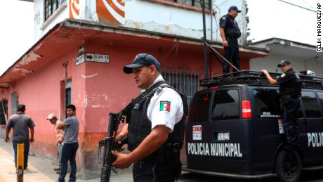 Municipal police stand guard at a forensic office where the bodies of the Mixtla de Altamirano mayor, her husband and her driver were taken after a drive-by shooting.