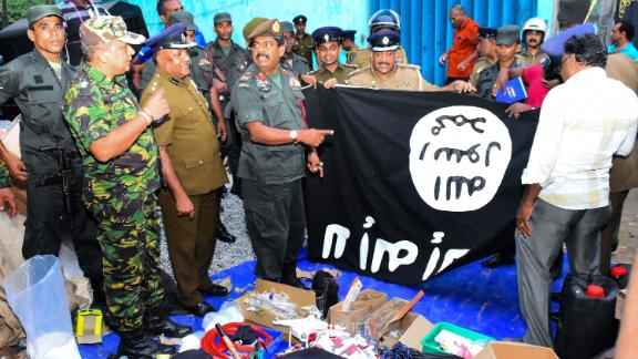 Security personnel display seized items, including an ISIS flag, in Friday