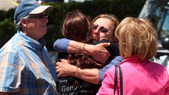 Members of the Chabad synagogue hug as they gather near the Altman Family Chabad Community Center, Saturday, April 27, 2019 in Poway, Calif. A shooting at a synagogue outside San Diego where worshippers were celebrating the last day of Passover sent multiple people to the hospital Saturday, but the extent of their injuries was not clear, officials said. (Hayne Palmour IV/The San Diego Union-Tribune via AP)