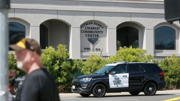 Neighborhood residents and members of the media stand before the Chabad of Poway Synagogue after the attack in Poway, California.