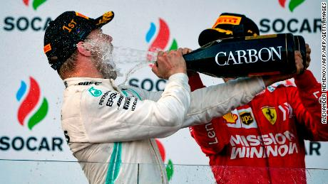 Winner Mercedes' Finnish driver Valtteri Bottas and third placed Ferrari's German driver Sebastian Vettel celebrate on the podium after the Formula One Azerbaijan Grand Prix in Baku on April 28, 2019. (Photo by Alexander NEMENOV / AFP)        (Photo credit should read ALEXANDER NEMENOV/AFP/Getty Images)
