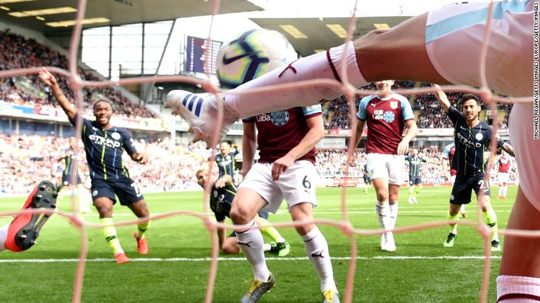 Burnley's Matthew Lowton fails to clear Sergio Aguero's shot in time.
