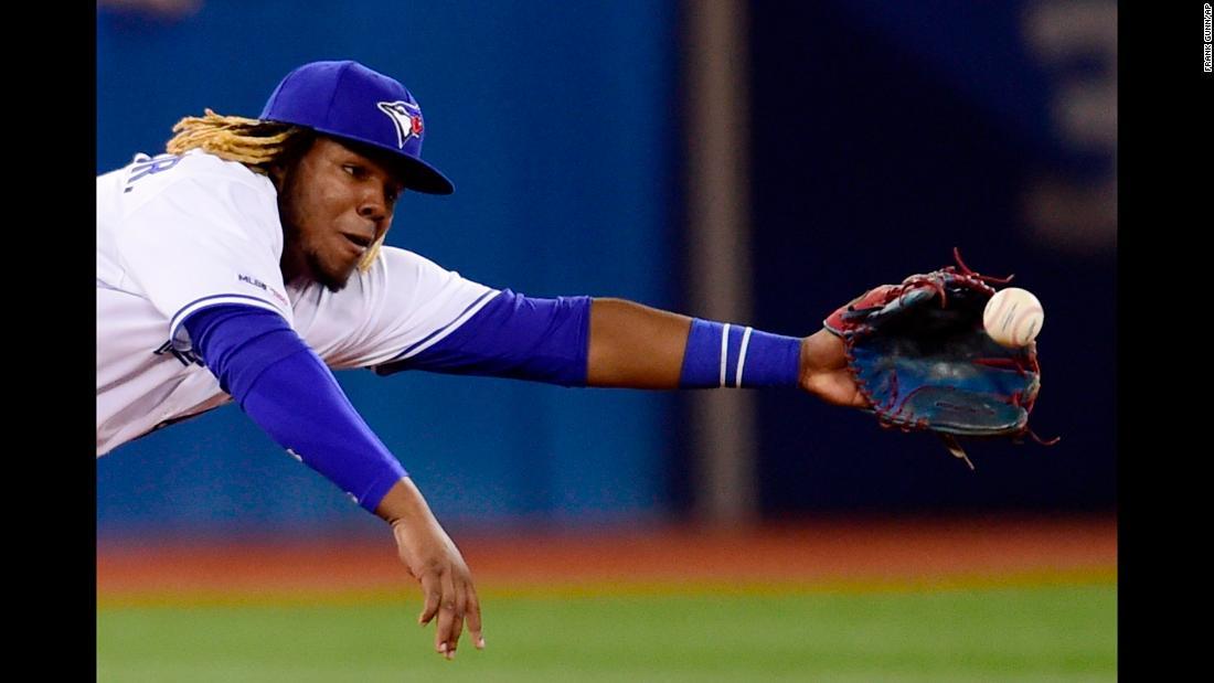 Toronto Blue Jays third baseman Vladimir Guerrero Jr. dives for a single by Oakland Athletics' Ramón Laureano during eighth-inning of a baseball game in Toronto on Friday, April 26.