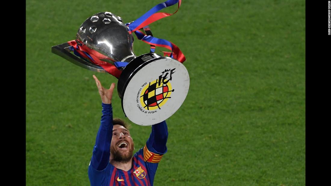 Barcelona's forward Lionel Messi raises the La Liga trophy as he celebrates becoming La Liga champions after winning the Spanish League football match between FC Barcelona and Levante UD at the Camp Nou stadium in Barcelona on Saturday, April 27.