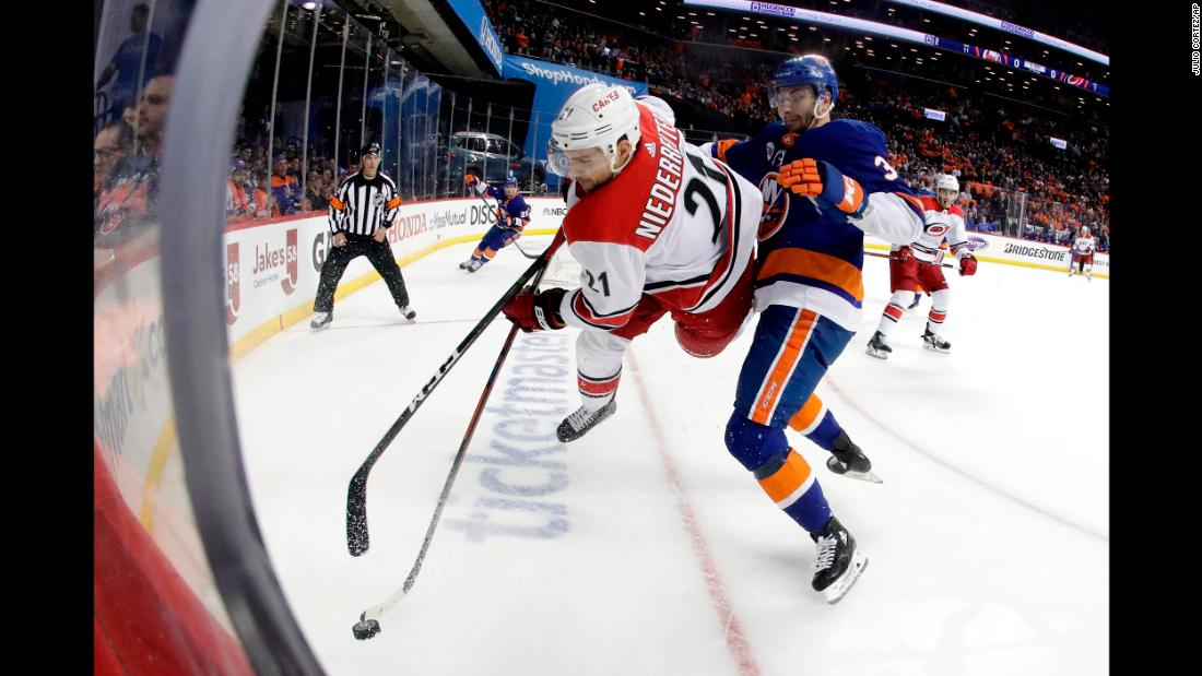 Carolina Hurricanes right wing Nino Niederreiter, left, of Switzerland, goes airborne while taking a hit from New York Islanders defenseman Adam Pelech during the first period of Game One of an NHL hockey second-round playoff series in New York on Friday, April 26.