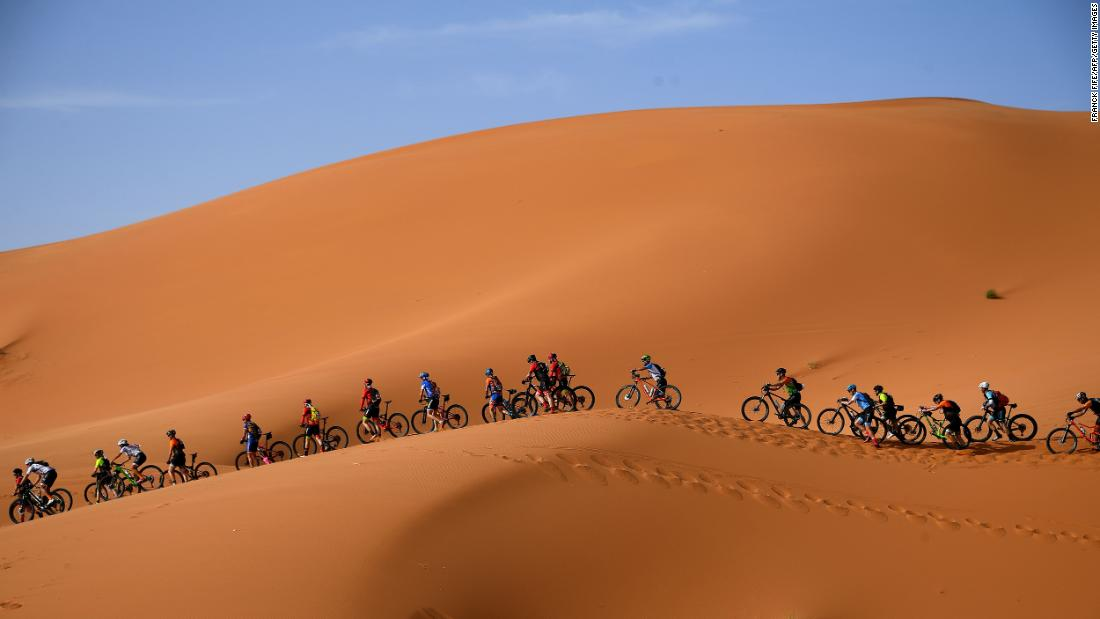 Competitors ride their bikes along sand dunes during the Stage One of the 14th edition of Titan Desert 2019 mountain biking race around Merzouga in Morocco on Sunday, April 28.