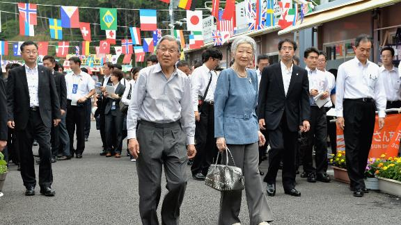 Akihito and Michiko tour shops in Minamisanriku, Japan, in July 2014. They offered encouragement to store owners who were affected by the earthquake and tsunami in 2011.