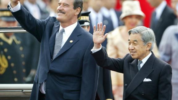 Akihito and Mexican President Vicente Fox wave to people while Fox visited Tokyo in 2003.