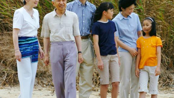 Akihito and Michiko walk on a beach in Shimoda, Japan, in 2004. Joining them were their son Fumihito and Fumihito