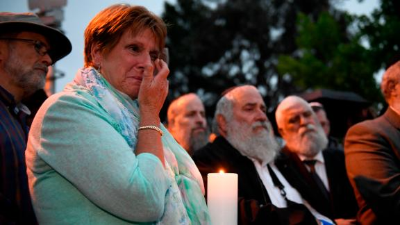 A woman cries during a candlelight vigil held for victims of the Chabad of Poway synagogue shooting, Sunday, April 28, 2019, in Poway, Calif.