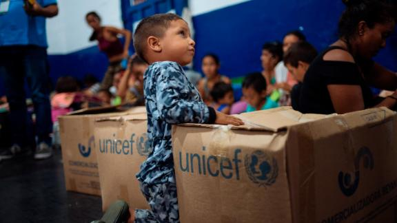On 24 April 2019 in Cucuta in Colombia, children play near boxes of UNICEF humanitarian supplies at the Samaritan's Purse resting point for walkers who will continue their journey from Venezuela by foot.