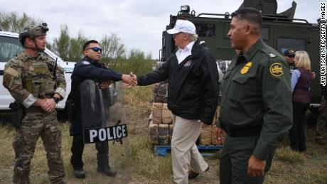 US President Donald Trump(C) greets a policeman with Border Patrol agents,and military after his visit to US Border Patrol McAllen Station in McAllen, Texas, on January 10, 2019. - Trump traveled to the US-Mexico border as part of his all-out offensive to build a wall, a day after he stormed out of negotiations when Democratic opponents refused to agree to fund the project in exchange for an end to a painful government shutdown. (Photo by Jim WATSON / AFP)        (Photo credit should read JIM WATSON/AFP/Getty Images)