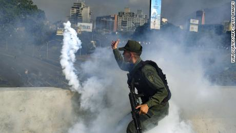 TOPSHOT - A member of the Bolivarian National Guard supporting Venezuelan opposition leader and self-proclaimed acting president Juan Guaido throws a tear gas canister during a confrontation with guards loyal to President Nicolas Maduro's government in front of La Carlota military base in Caracason April 30, 2019. - Guaido said on Tuesday that troops had joined his campaign to oust President Nicolas Maduro as the government vowed to put down what it called an attempted coup. (Photo by Yuri CORTEZ / AFP)        (Photo credit should read YURI CORTEZ/AFP/Getty Images)