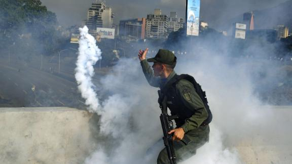 TOPSHOT - A member of the Bolivarian National Guard supporting Venezuelan opposition leader and self-proclaimed acting president Juan Guaido throws a tear gas canister during a confrontation with guards loyal to President Nicolas Maduro