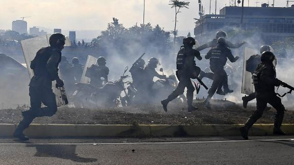 Military members loyal to Maduro run under a cloud of tear gas after being repelled with rifle fire from pro-Guaido military members on April 30.