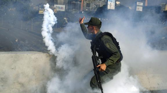 A pro-Guaido military member throws a tear-gas canister during a confrontation with guards loyal to Maduro.