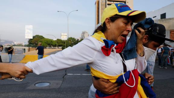 A woman affected by tear gas is aided by fellow opponents of Maduro.